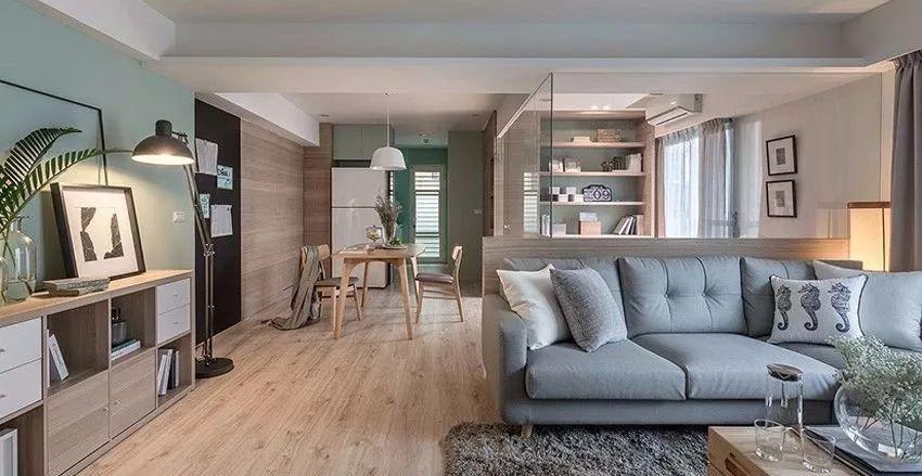 蓝灰色主沙发依靠书房的半高木墙,过道一侧设置玄关柜,增添客厅