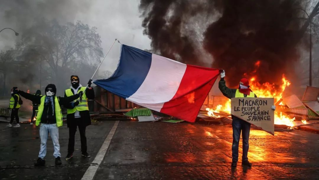 """法国总统马克龙为实走《巴黎气候制定》,将柴油税每公升上调了6.2%。燃油税上涨导致了油价飙升,引发民多不悦,从11月17日开起爆发抗议活动,抗议者同一穿上荧光黄背心行为识别物,所以被称作""""黄背心""""行动。"""
