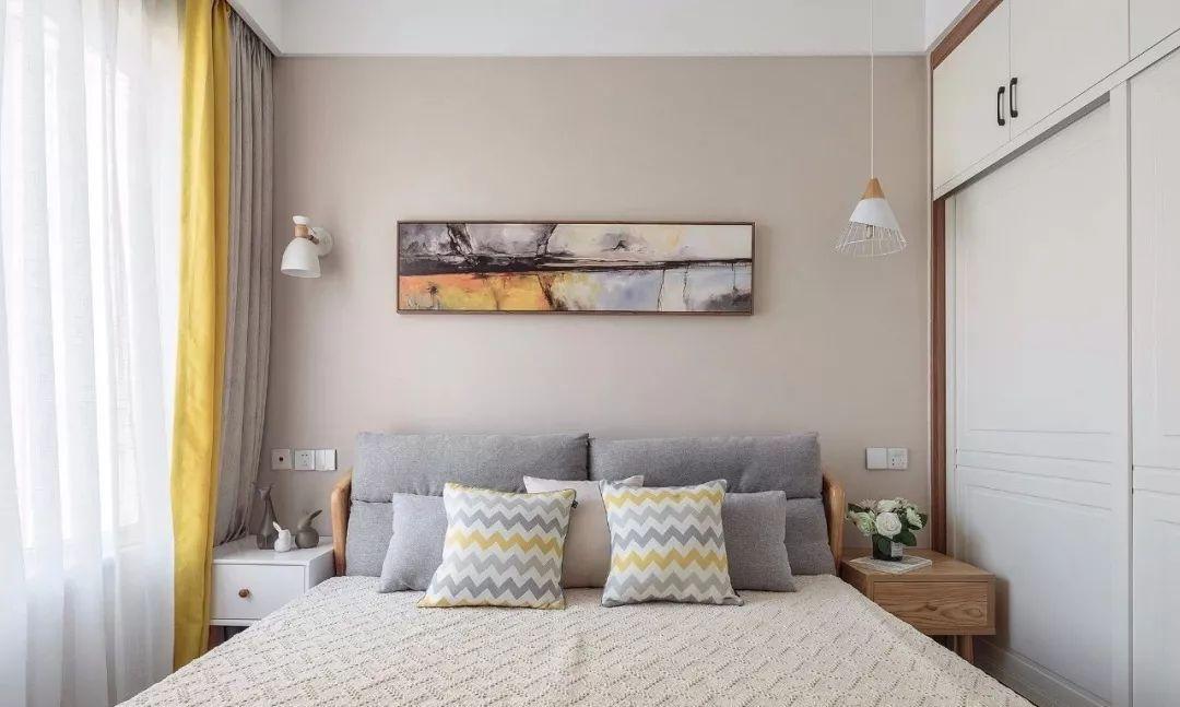 主卧延续浅咖色墙面,挂一幅抽象装饰画,辅以壁灯与悬挂式吊灯作卧室照