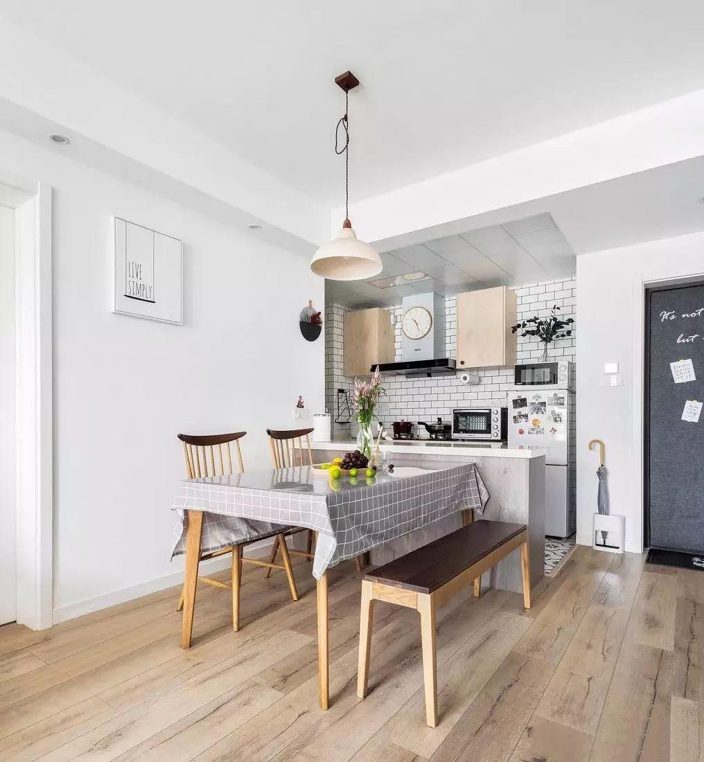 餐桌铺一块灰格子桌布,放上水果与花束,营造了轻松自在的休闲氛围.图片