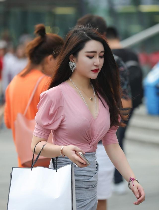 模特身穿粉色上衣灰色裙子青春時尚,表情高冷有點酷