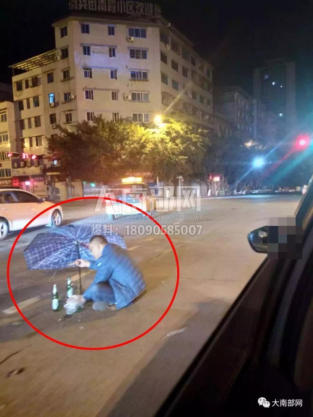 奇葩 深夜南充一男子在马路中间打着伞吃菜喝酒一个多小时 视频