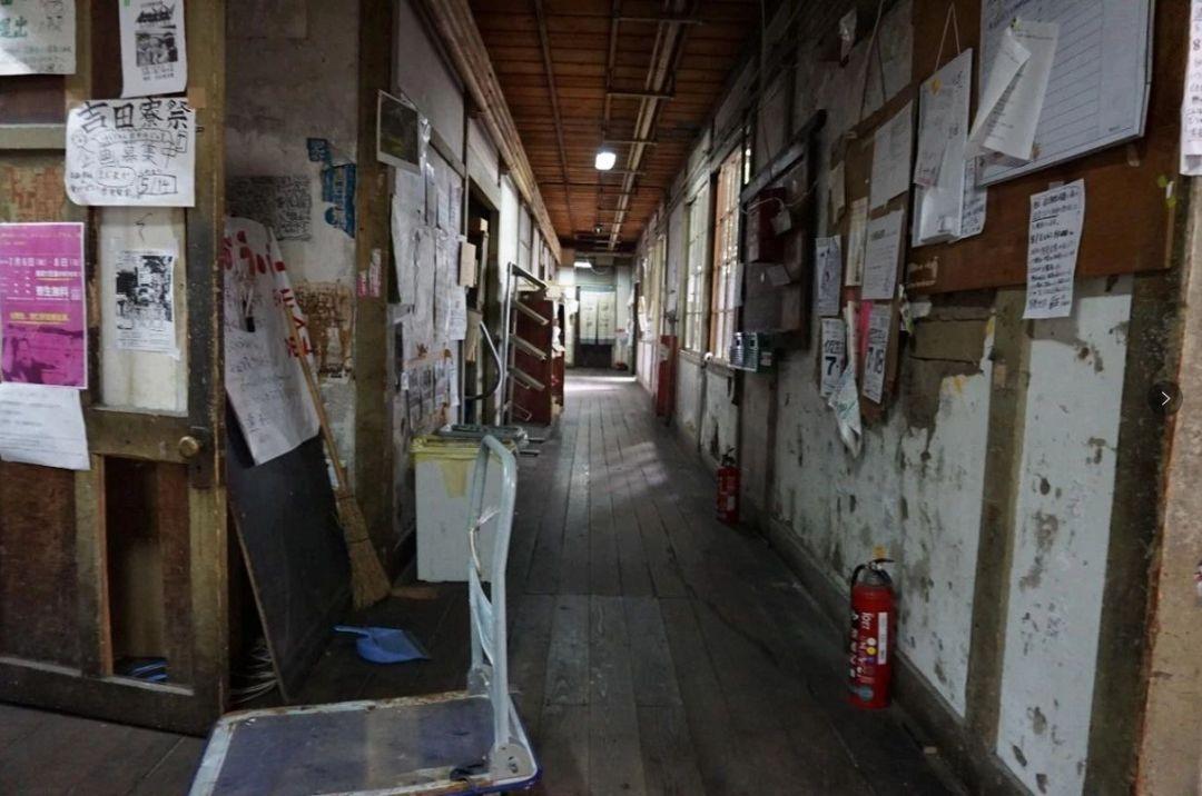 狭窄的走道两边堆满了生活,学习物品,中间留出供人行走的干净地面.