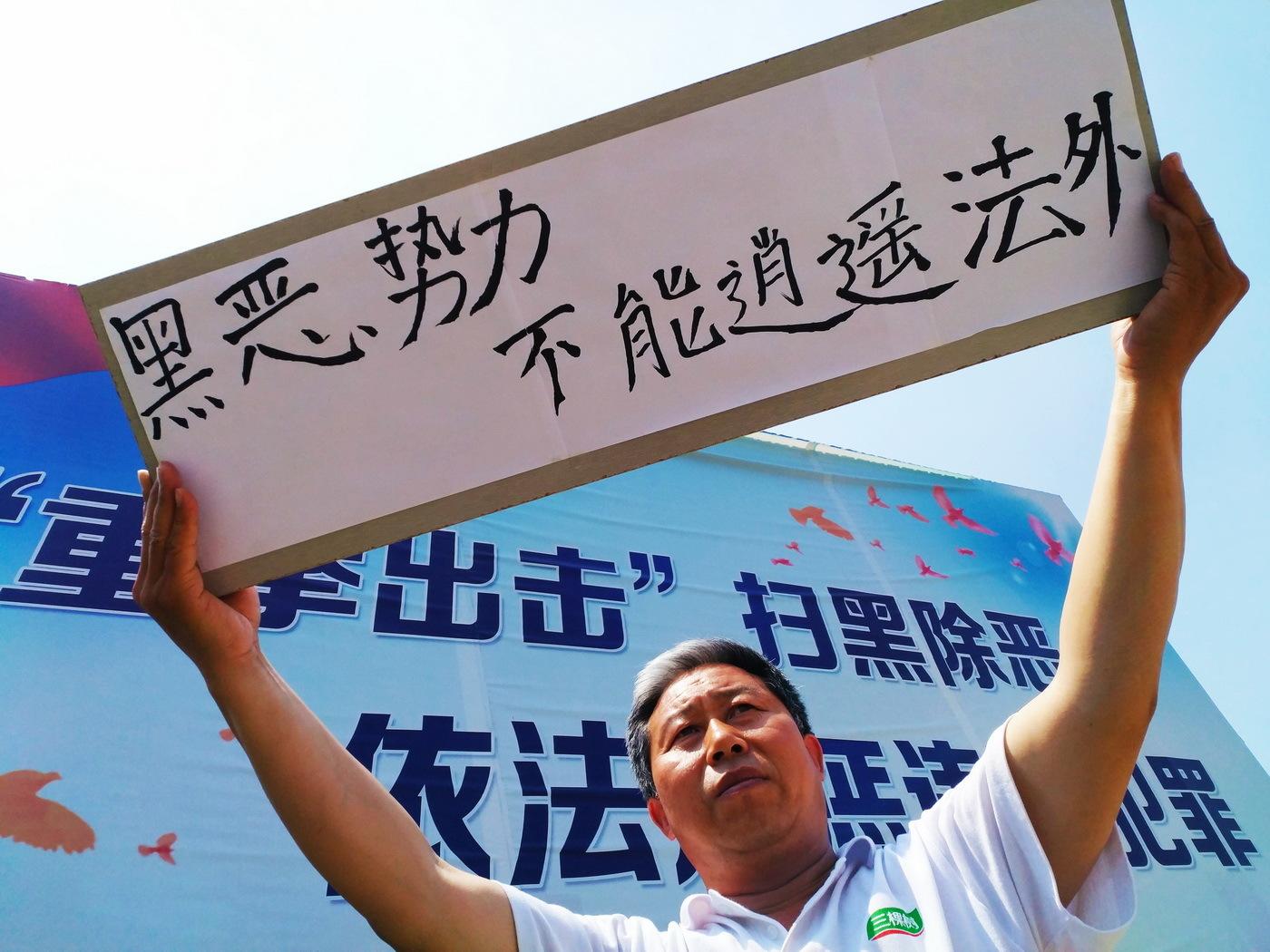"""山东阳信:男子街头高举""""黑恶势力不能逍遥法外"""""""