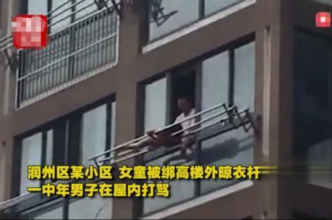 10岁女孩被绑在高楼外的晾衣杆上,父亲站在室内对她又打又骂