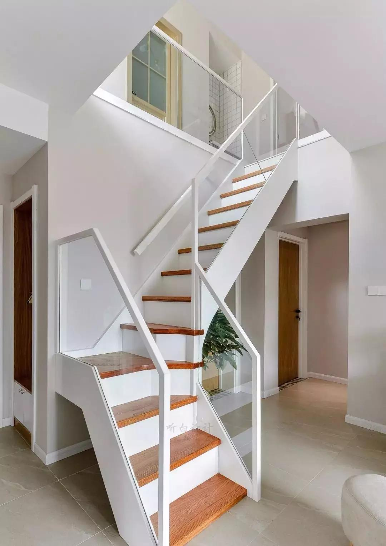 通往阁楼楼梯,白色楼梯主结构配木面踏步与玻璃护栏,确保安全的