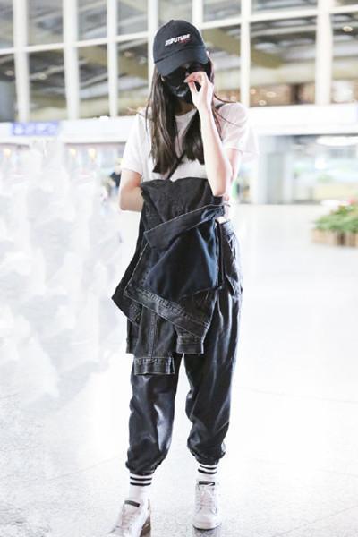 迪丽热巴现身机场,白色T恤带口罩休闲简单,下身穿着很吸睛
