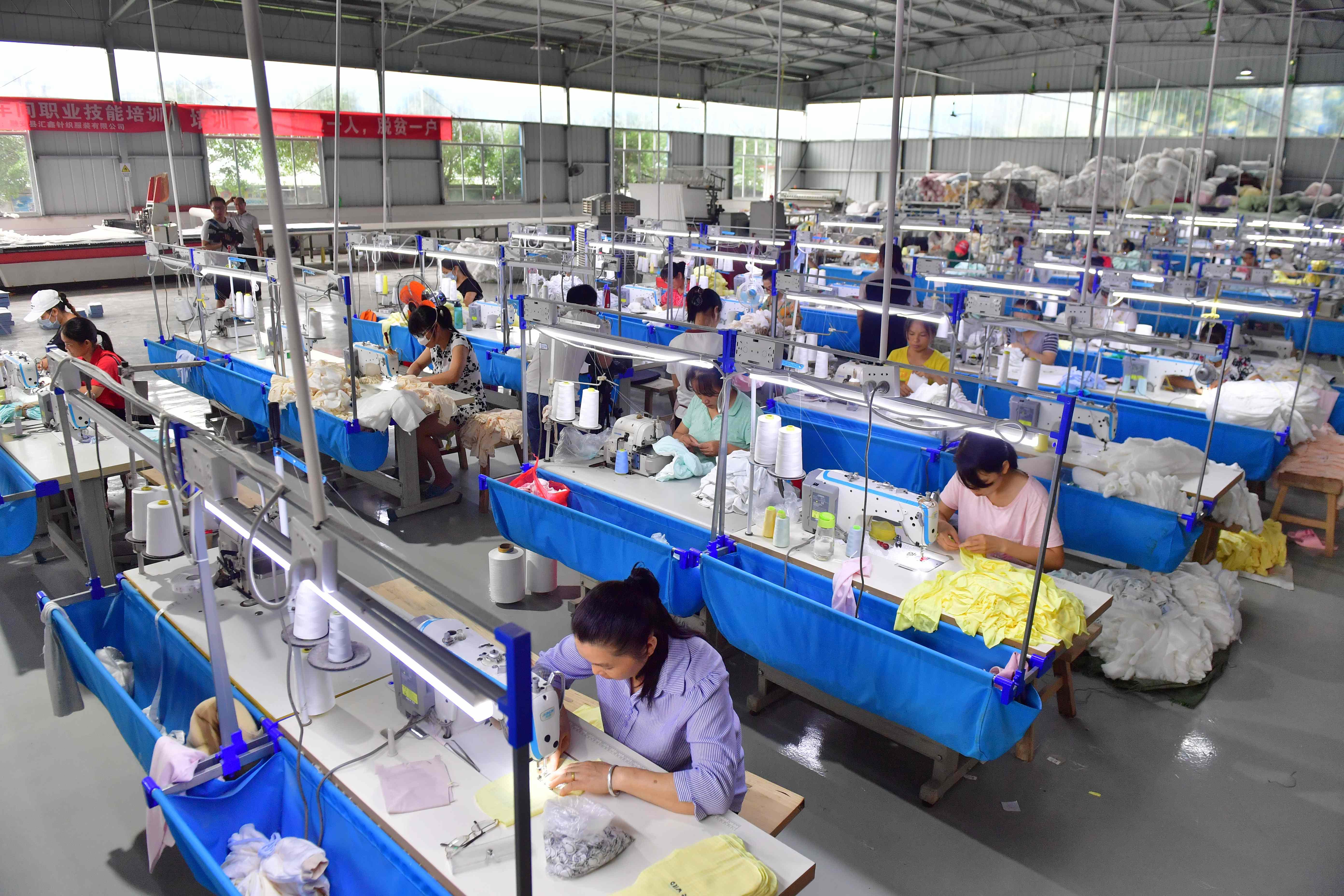7月15日,工人在广西柳州市融安县隘面扶贫微车间缝制服装.图片