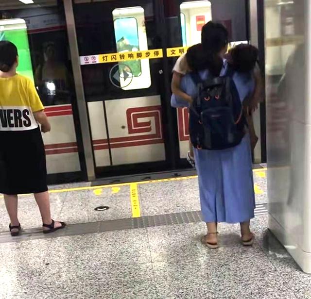 地铁站台一位妈妈抱俩娃的偷拍照火了,网友泪目:小身躯,大能量