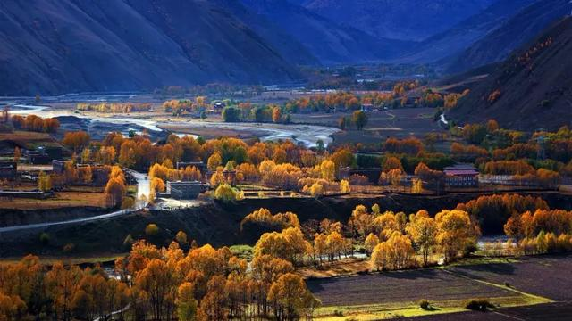 弯弯的小溪,金黄的柏杨,山峦连绵起伏,藏寨散落其间,炊烟袅绕,宛如置