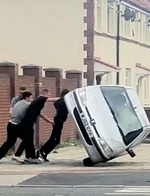 英國四名男孩街頭掀翻一輛汽車 大笑著逃跑
