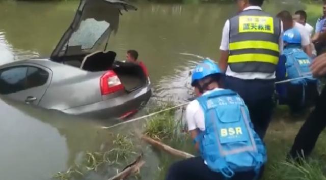 忘拉手刹轿车溜进河中,车主看了半天热闹,恍然大悟:这车是我的