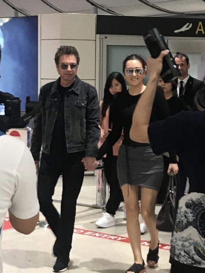 54岁巩俐与71岁老公十指相扣现身机场,穿超短裙秀长腿超幸福