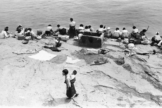 图为身穿当地服饰的韩国女子正在河边洗衣服,边上有人把已经洗好的衣服就放在这石头上晒了起来,这样晒衣服倒是省事.