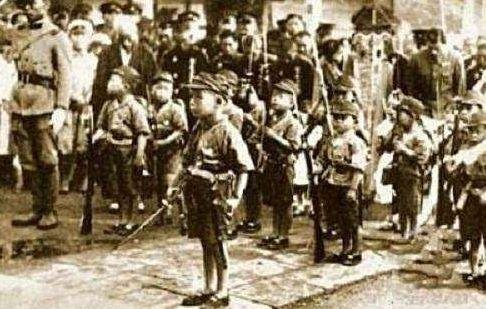 长崎轰炸后,一个小男孩背着他的弟弟走向火葬场