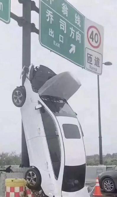 杭州:女子将车垂直开上标志杆