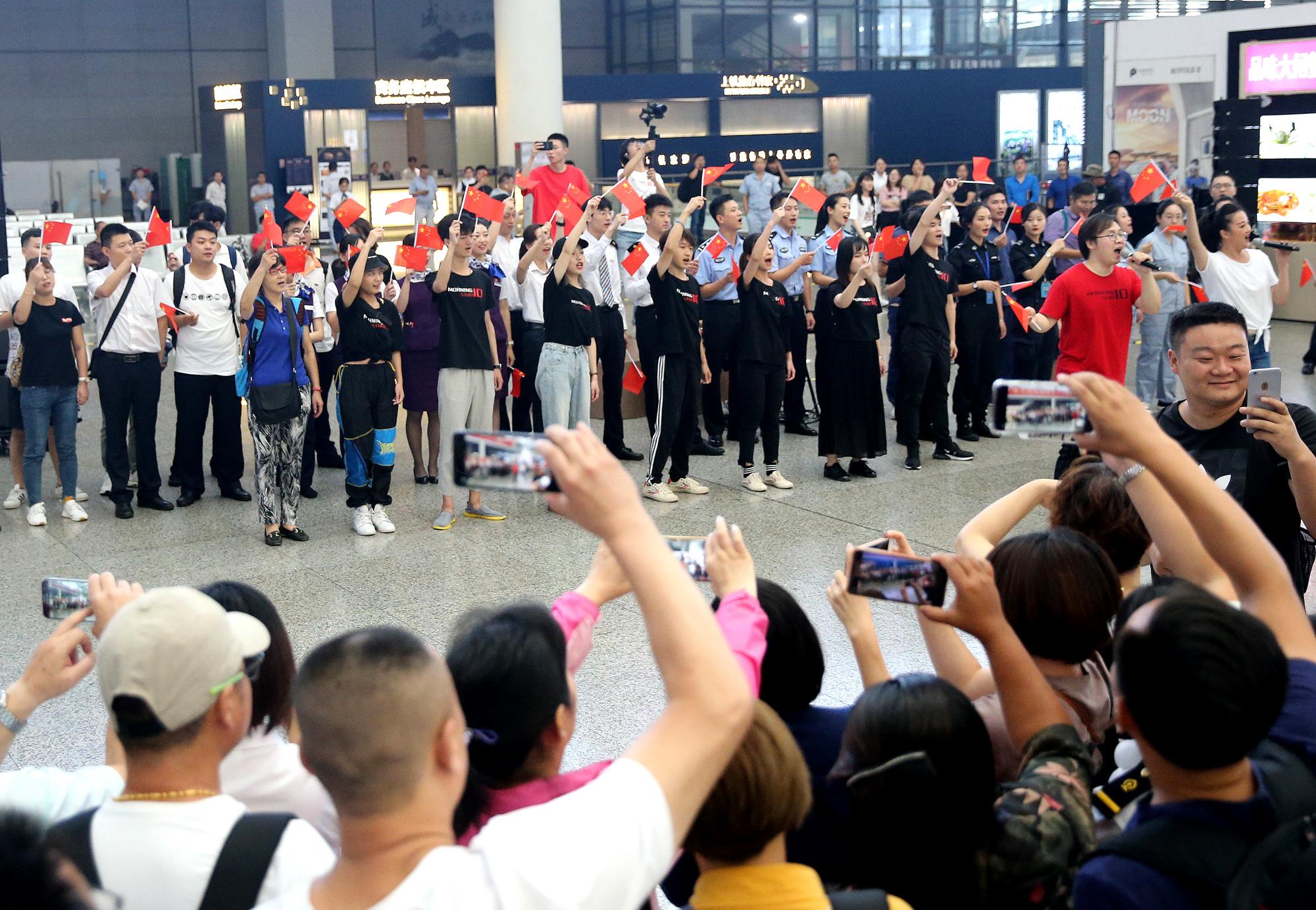 """上海:车站""""快闪""""歌唱祖国"""