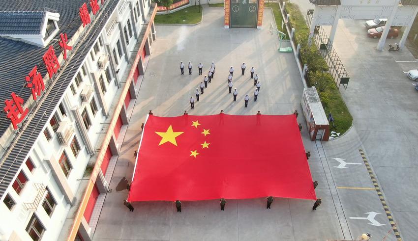 上海金山消防指战员托举起160平米巨幅国旗 传递浓浓爱国情