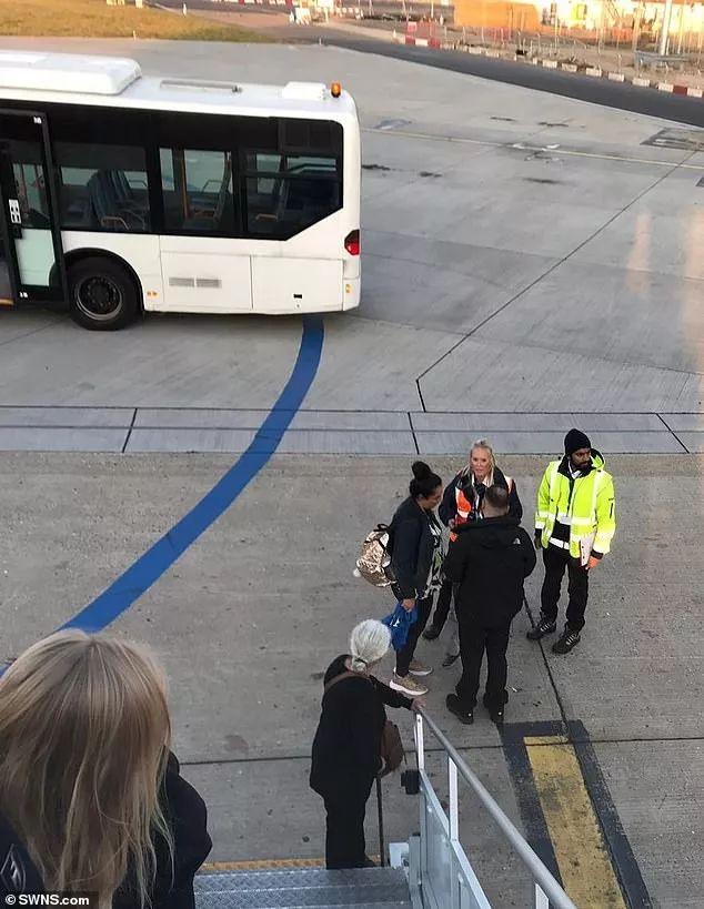 飞机正在加油,一位登机的乘客点燃了一根烟