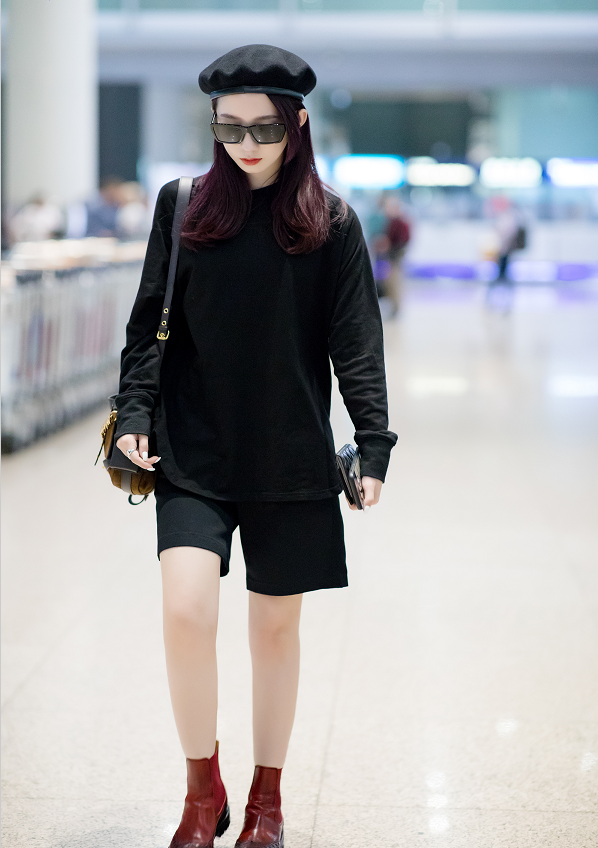 孟美岐穿黑毛衣脚踩小短靴,头戴蓓蕾帽黑超遮面,造型十分霸气!