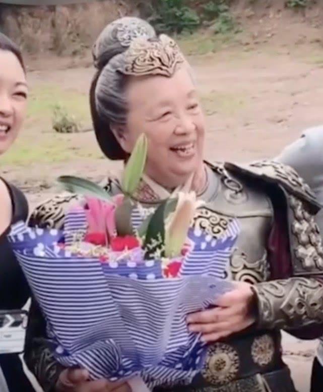 83岁李明启头发花白演古装剧,一身铠甲精神矍铄捧花笑得眼弯弯