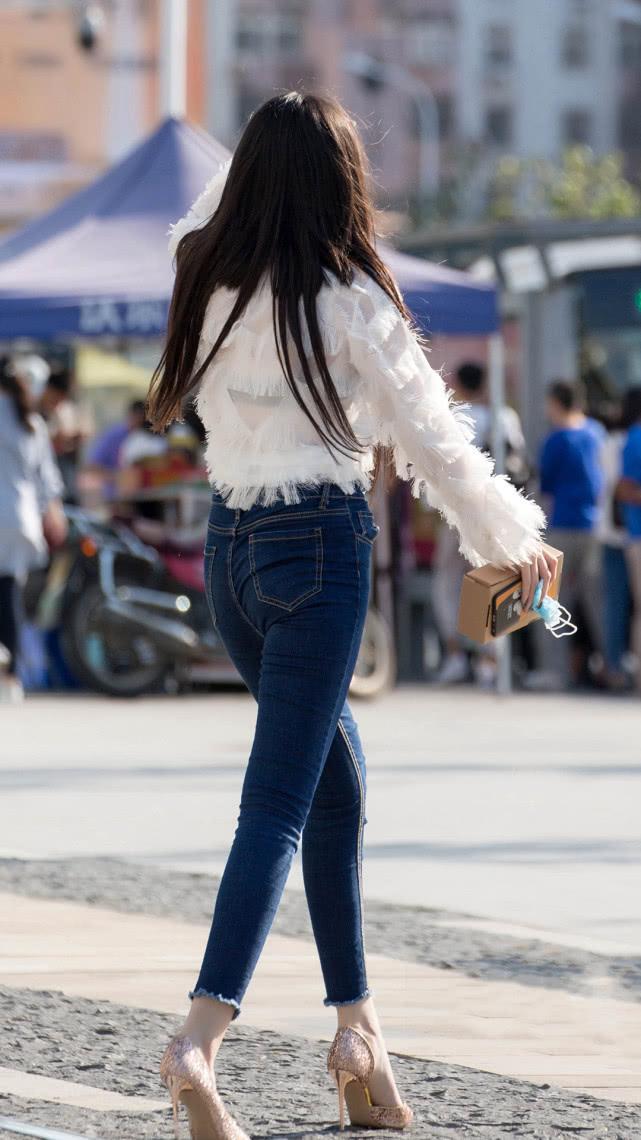 街拍美女:个性羽毛上衣,搭配紧身牛仔裤,苗条身材专属穿搭插图(2)