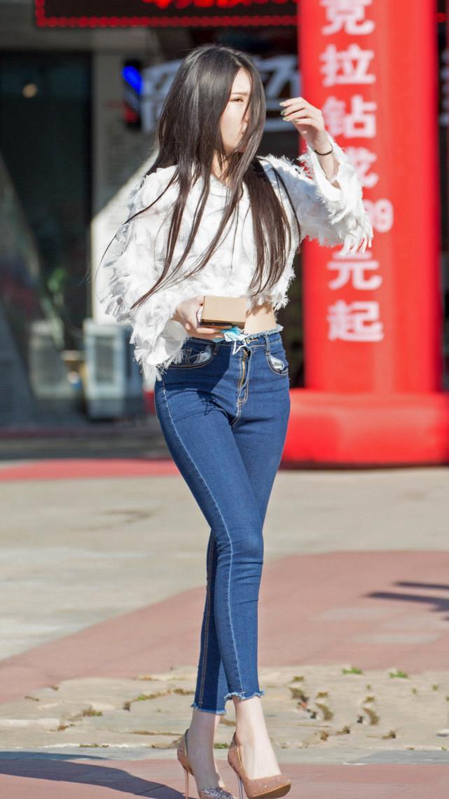 街拍美女:个性羽毛上衣,搭配紧身牛仔裤,苗条身材专属穿搭插图(1)