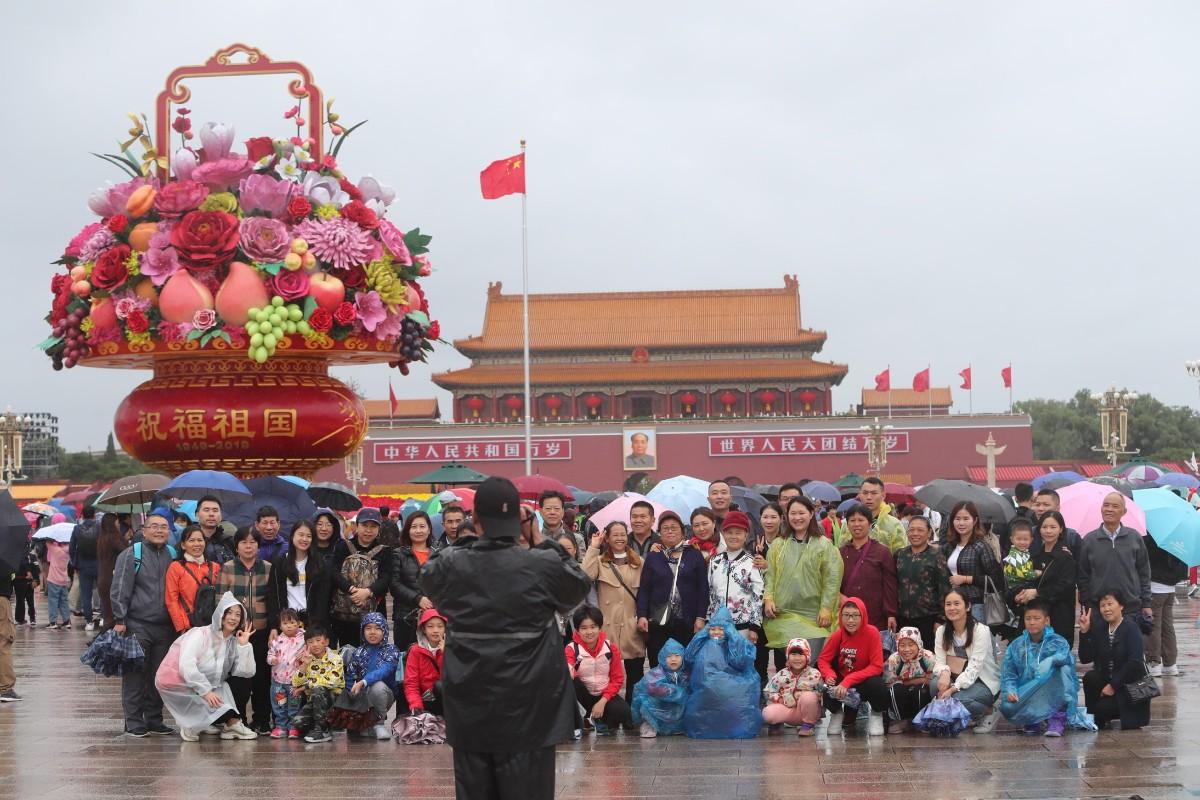 天安门广场,下雨天,听说雨伞与大花篮更配哦……