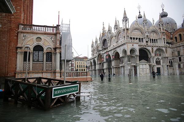 威尼斯又被淹,居民站在水中买面包