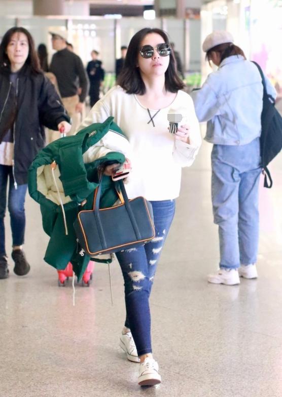 张靓颖穿烂大街的白T配牛仔裤,不追求大牌不凹造型,堪称机场清流