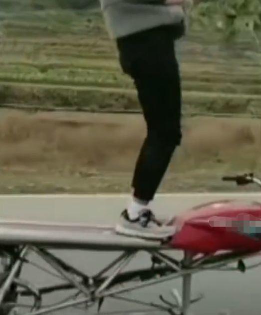 男子双手脱把在一辆非法改装的摩托车上站立驾驶,被网友举报
