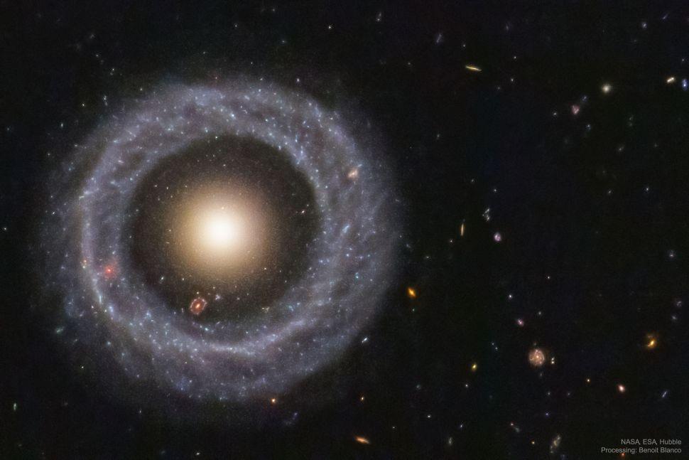 这个环状星系(霍格天体)外侧是一道由蓝色年轻恒星组成的环,而中心附近是由一些古老而黯淡的恒星作为内核.