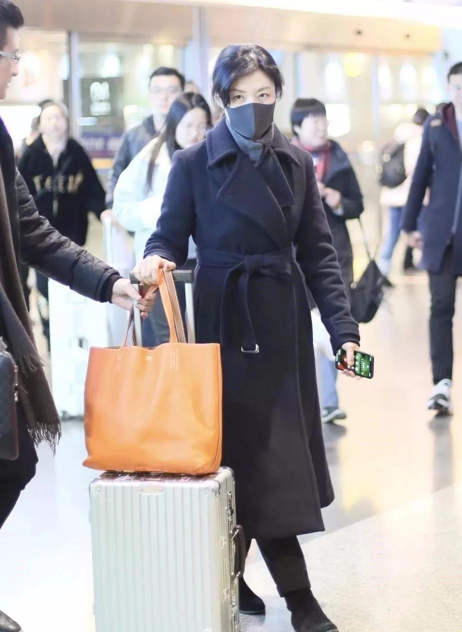 51周涛现身长沙机场,穿黑大衣真有范,央视主持就她气质好!