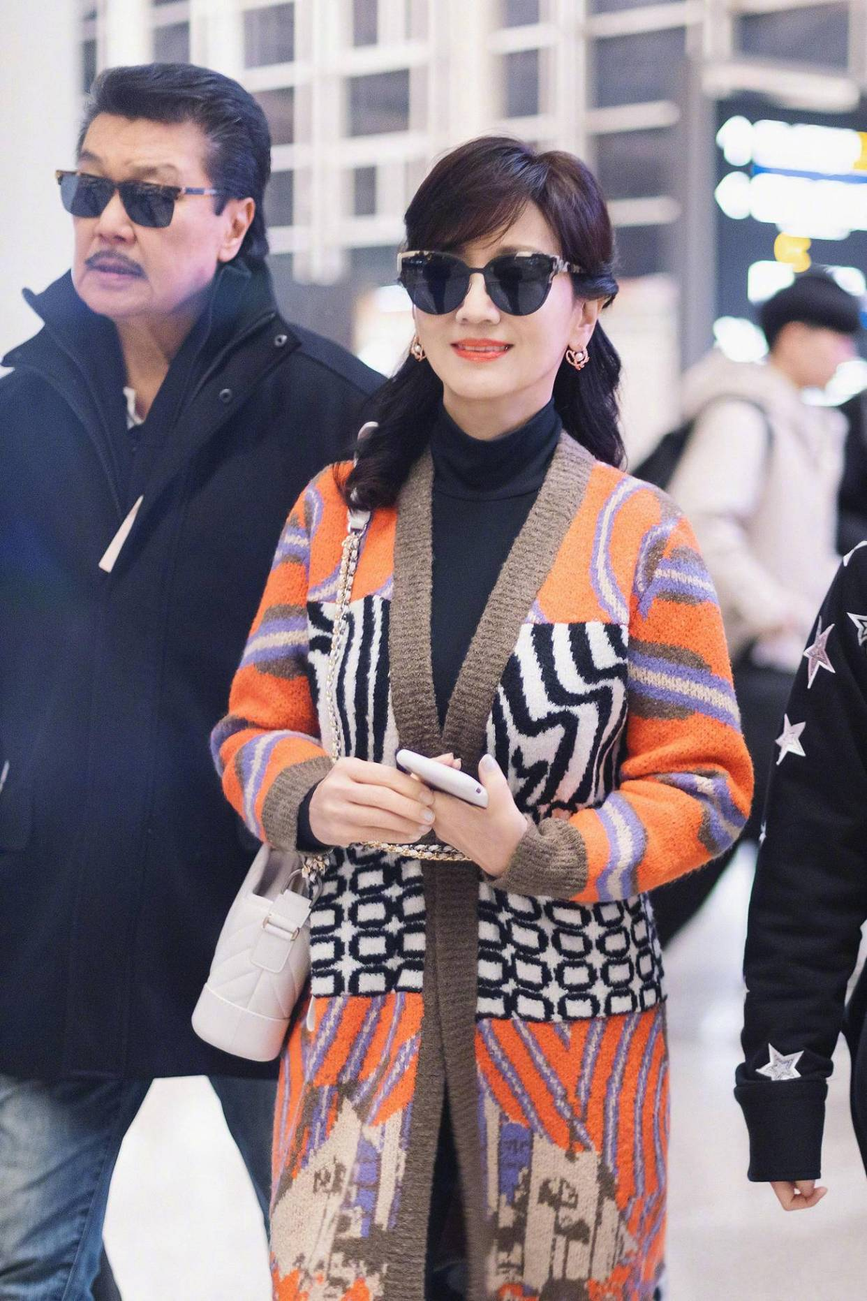 赵雅芝黑色打底配亮色针织外套,包包背带扎腰好时髦,老公依旧帅
