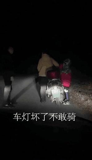 男子开车跟在骑电动车的母子身后 为其照亮前路