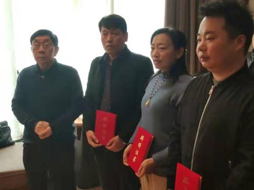 中国国画院华东分院院长徐作康(左一)向弟子们颁发拜师证书
