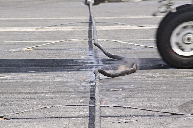 阻拦索能致命?美军26吨舰载机降落航母,8名小绿人双腿被扫断