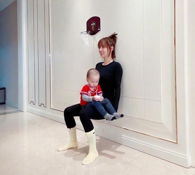 张嘉倪靠墙深蹲,小儿子坐在腿上帅气出镜