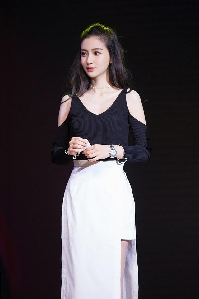 杨颖身穿黑色露肩上衣性感优雅,搭配白色开衩裙,造型简约时尚