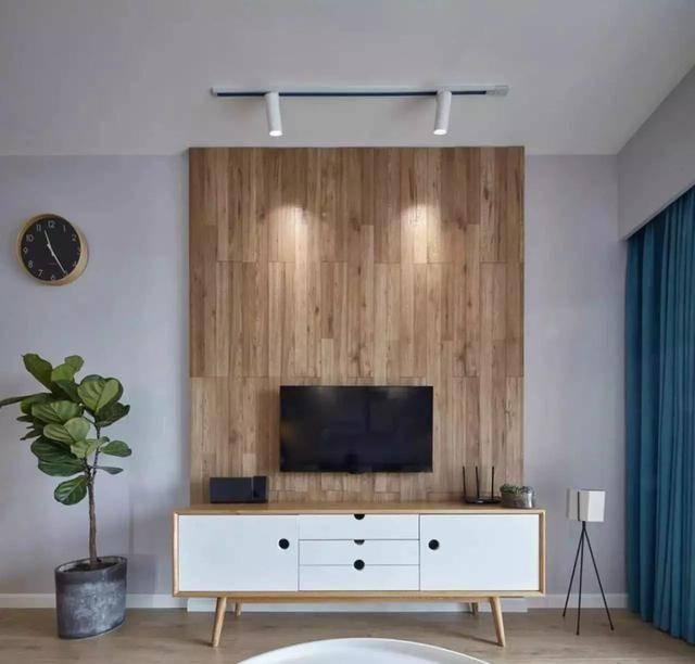 电视背景墙用与地板同色系的木板铺贴,整体感非常强,浑然一体,而且