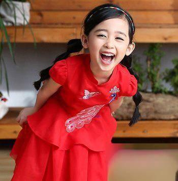 穿喜庆大红色新年服的小女孩,妈妈将小女孩黑色长发大偏分之后,扎成烤