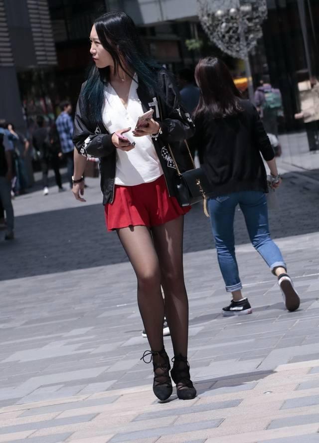 蓝月帝国街拍:拿着两个手机的黑丝袜美女