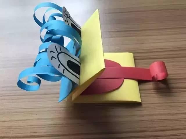 制作步骤: 1,用卡纸剪出人物的上半身,脖子和脑袋,并贴在纸盒上.