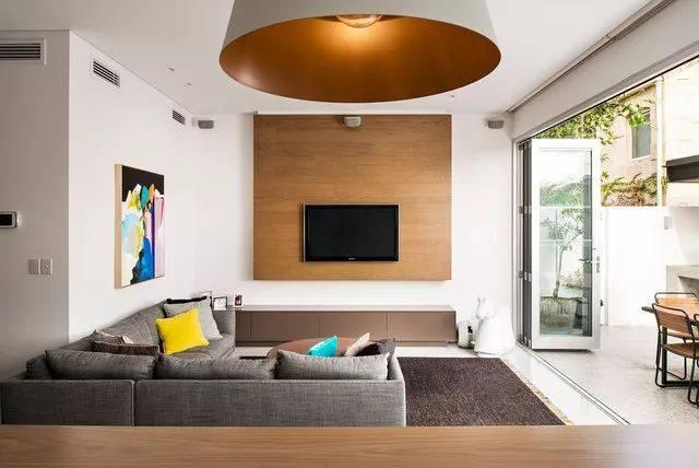 以木饰面作为电视背景墙, 能为冰冷的空间注入一丝温暖的质感.
