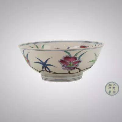 碗通体斗彩装饰,碗内底青花双圆圈内绘团花纹,内外壁绘斗彩缠枝秋葵纹