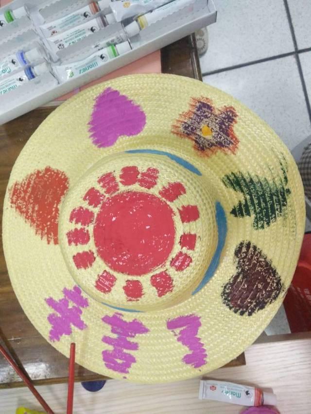 大学生志愿者教小学生手绘草帽赠环卫工人
