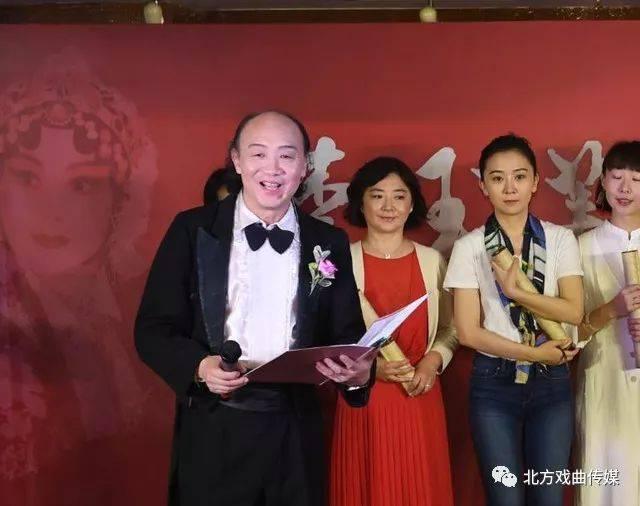 李玉芙先生从主持人手里接过吴松林先生赠送的剧照图片