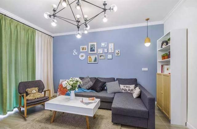 客厅沙发的蓝色的背景墙上做了照片墙的设计,灰色的布艺沙发搭配抱枕图片