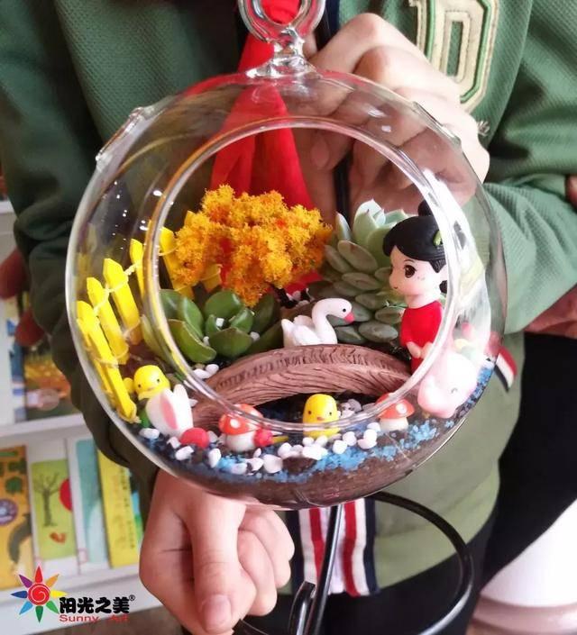 仔细玻璃瓶中铺上沙石和绿植 将袖珍植物小心植于瓶中 最后再放几个图片