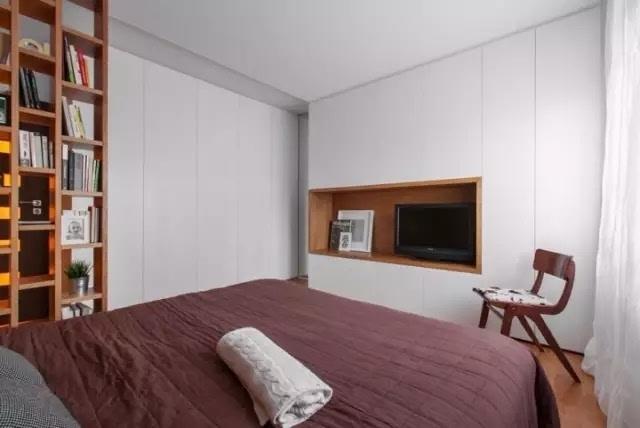卧室空间背景墙是原始自然的实木墙板,深棕色色调以及木纹体现材质的